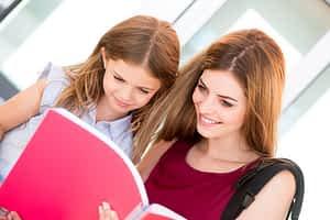 Little school girl showing sketchbook to her mother
